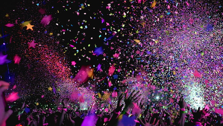 Hands reaching for colorful confetti at a club