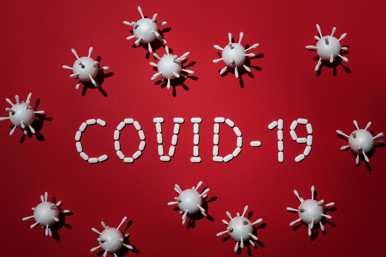 White Covid-19 text on red background with little virus symbols