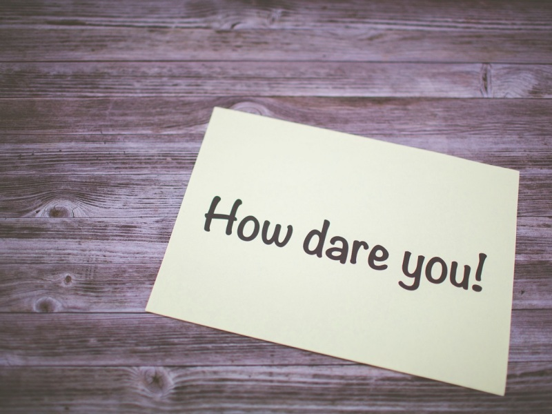 A post-it note on a table saying 'How dare you!'