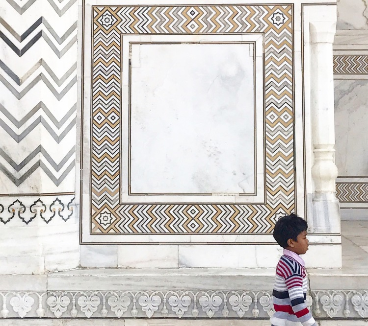 Small child walking in front of marble patterns