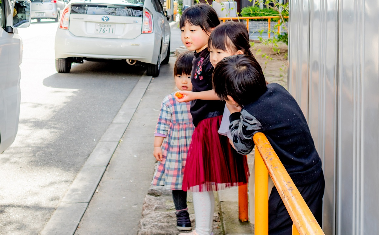 Group of young Japanese children at the side of a street
