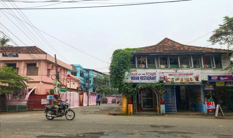 Motorbike driving past a restaurant in Kochi, Kerala
