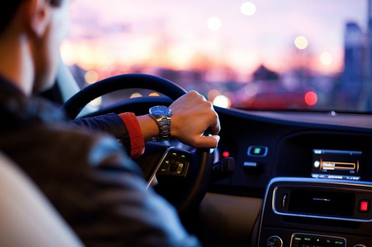 Man's hand on car steering wheel
