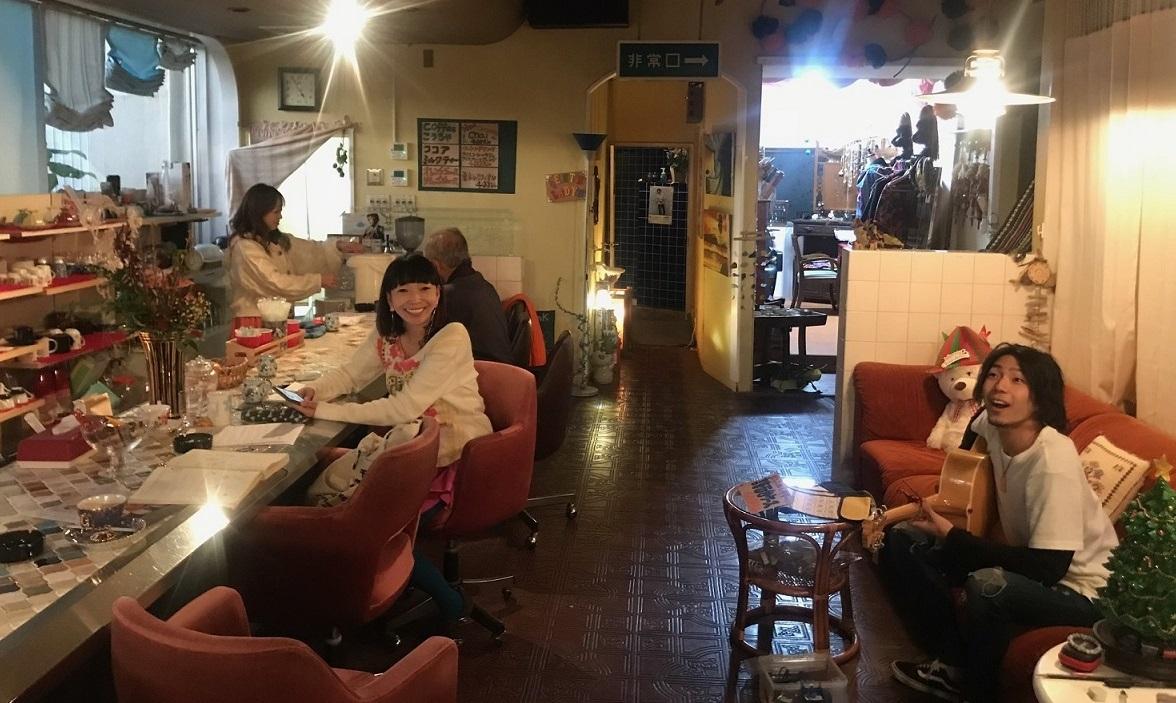 Guy playing guitar inside old Japanese cafe